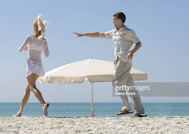 Couple chasing each other around parasol on beach