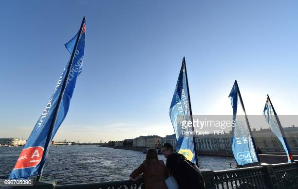 A couple chat on the Palace bridge on the Neva river on June 16 2017 in Saint Petersburg on the eve of the opening match of the FIFA Confederation Cup