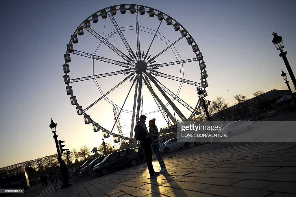 A couple chats next to a ferris wheel at sunrise on December 30, 2012 at the Concorde square in Paris.