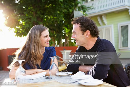 Couple chatting in outdoor restaurant : Bildbanksbilder