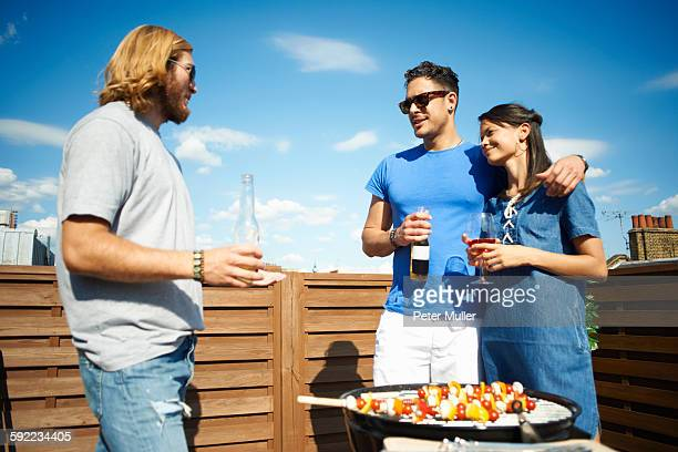 Couple chatting to male friend at rooftop party