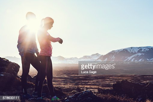 Couple check fitness tracker in beautiful scenery