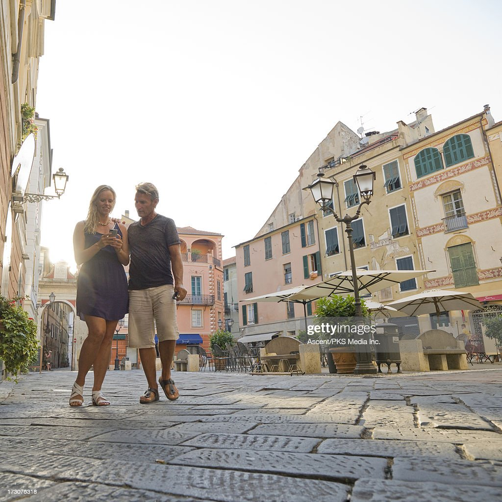 Couple check text while walking through piazza : Stock Photo