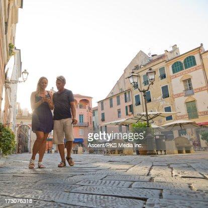 Couple check text while walking through piazza : Stock Photo