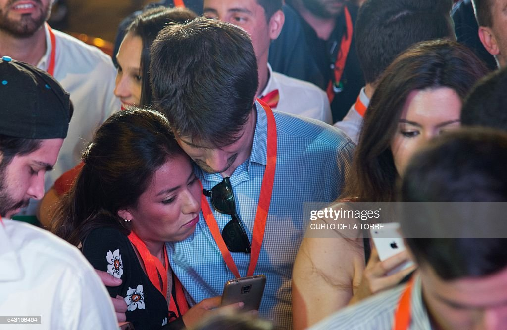A couple check their cell-phone as they wait for official results outside the center-right party Ciudadanos's headquarters during the Spanish general elections in Madrid, on June 26, 2016. Spain's second elections in six months was due to conclude on June 26 in much the same way as they did in December, with the incumbent conservatives winning tailed by the Socialist party, partial results showed. / AFP / CURTO