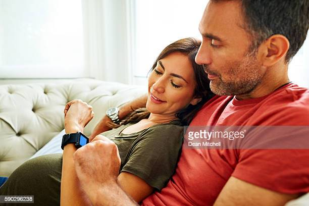 Couple checking condition of pregnancy in smartwatch