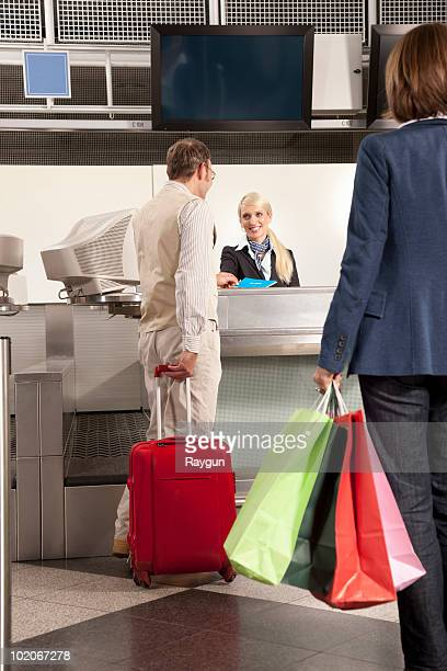A couple checking in with shopping bags