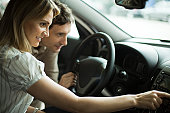 Couple checking out new car interior in dealership showroom