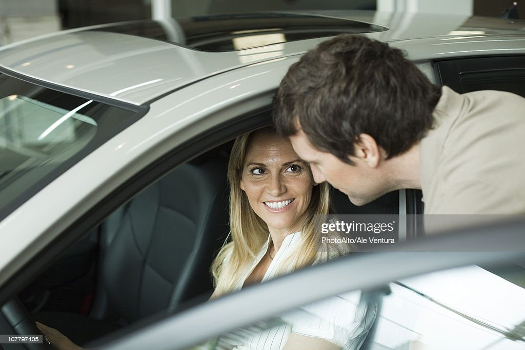 Couple checking out new cars in dealership showroom : Stock Photo