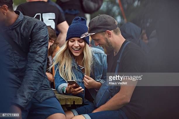 Couple checking phone at festival