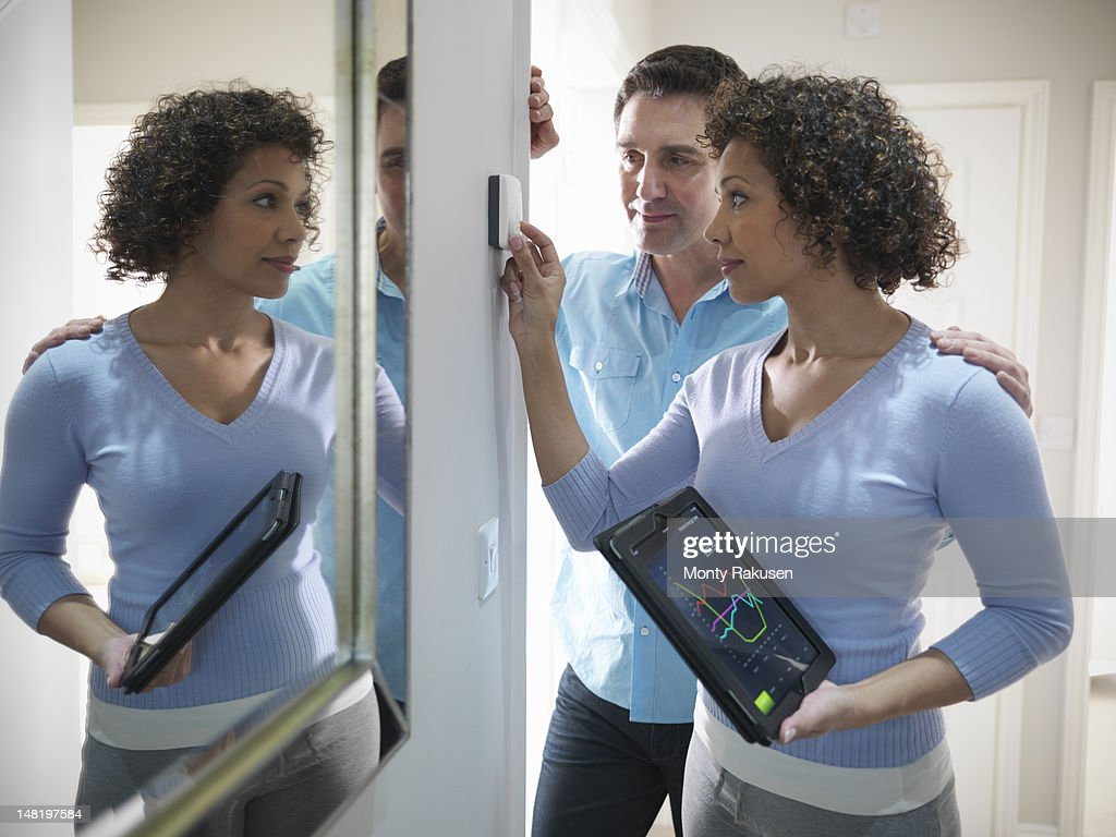 Couple checking thermostat with energy tracking application on digital tablet