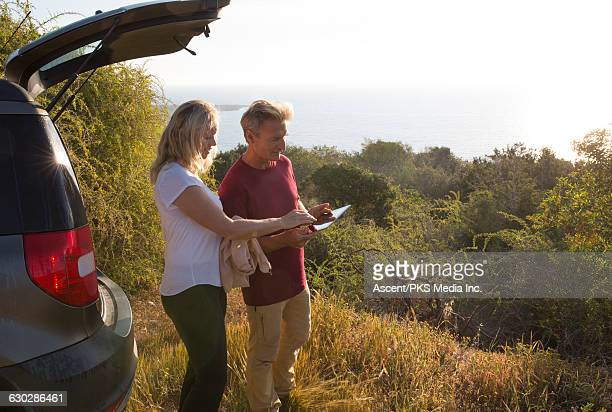 Couple checks digital tablet for direction, forest