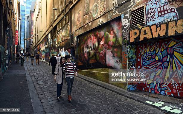 A couple checks their phone while walking through a lane adorned with graffiti in Melbourne on March 22 2015 AFP PHOTO / INDRANIL MUKHERJEE