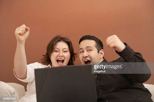 Couple cheering behind laptop