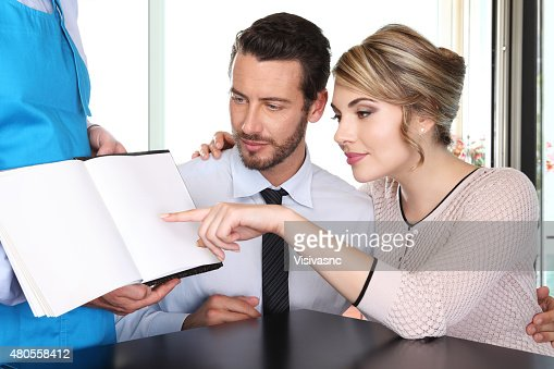 couple chooses from the menu : Stock Photo