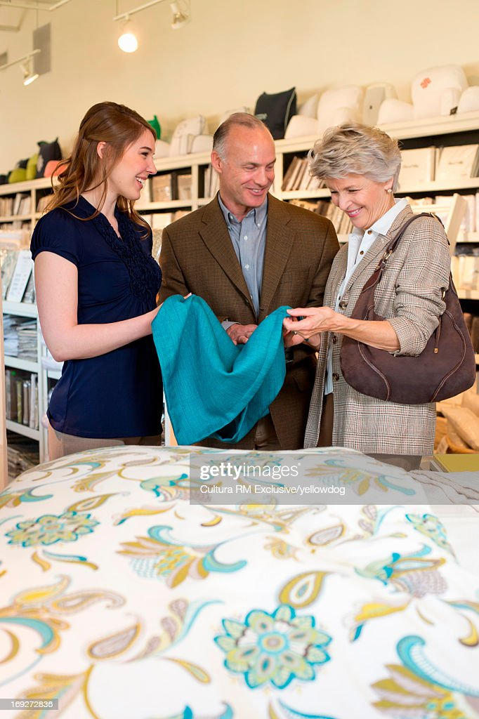 Couple choosing bedding in fabric shop with shop assistant : Stock Photo
