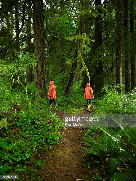 Couple choosing different paths on forest trail.
