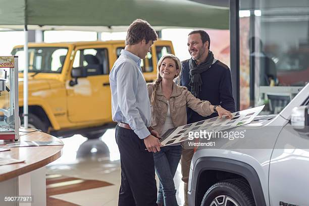 Couple choosing from color sample at car dealer