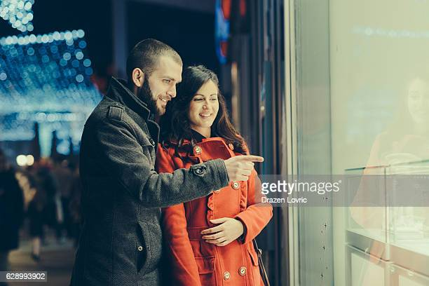 Couple choosing gifts together near the shop window