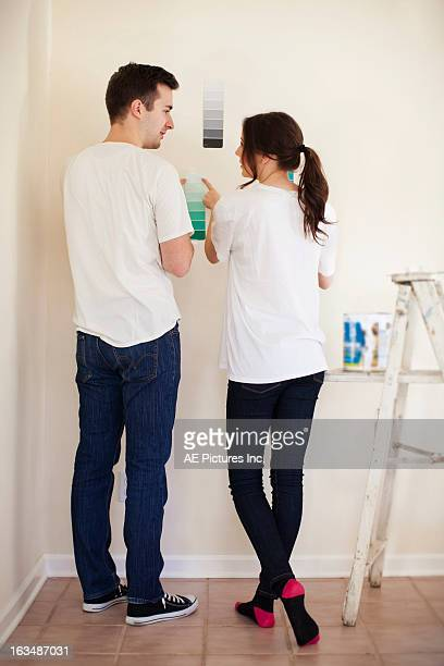 Couple choosing paint color at home