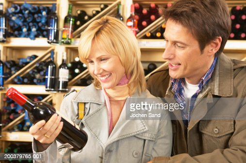 Couple choosing wine in supermarket, smiling, close-up : Stock Photo