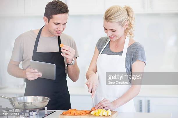 Couple chopping and tasting sliced vegetables in kitchen