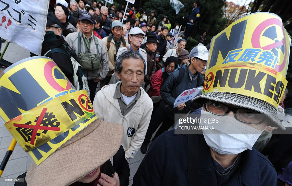 A couple clad in hats with anti-nuclear logos shout slogans during a rally denoucing nuclear power plants in front of the Diet building in Tokyo on November 11, 2012. Several thousand people took part in the rally. AFP PHOTO/Toru YAMANAKA