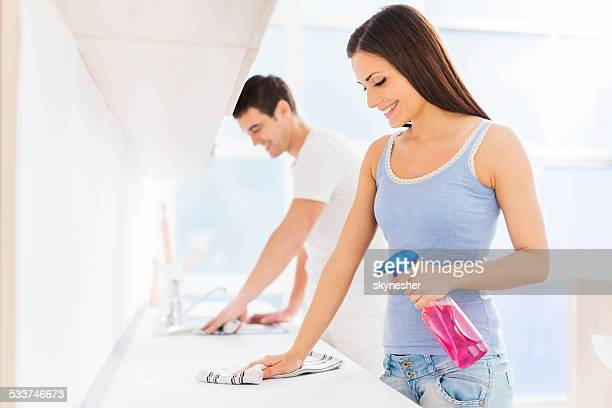 Couple cleaning kitchen.