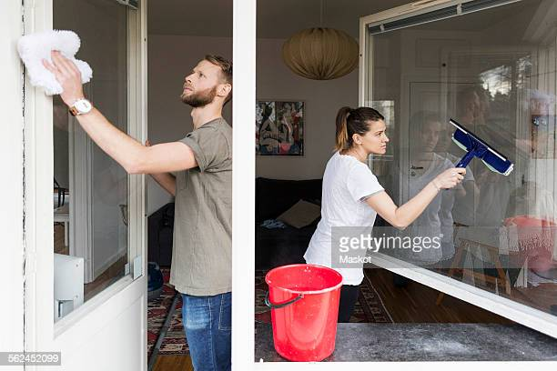 Couple cleaning window together at home