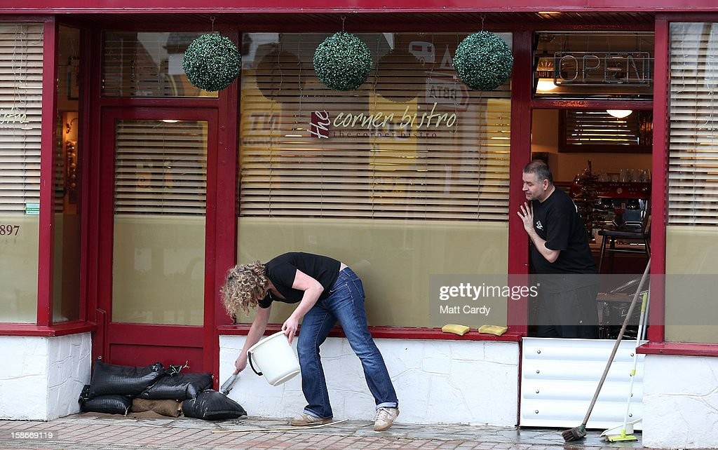 A couple clear up after flood waters entered their cafe in the centre of the Devonshire town of Braunton that was flooded yesterday on December 23, 2012 near Barnstaple, England. Flooding has brought further disruption to many parts of the UK including the South West of England that was particularly badly hit. The Met Office are warning of further bands of heavy rain tonight and the Environment Agency has issued 100s of flood warnings for England including one severe warning for Cornwall.
