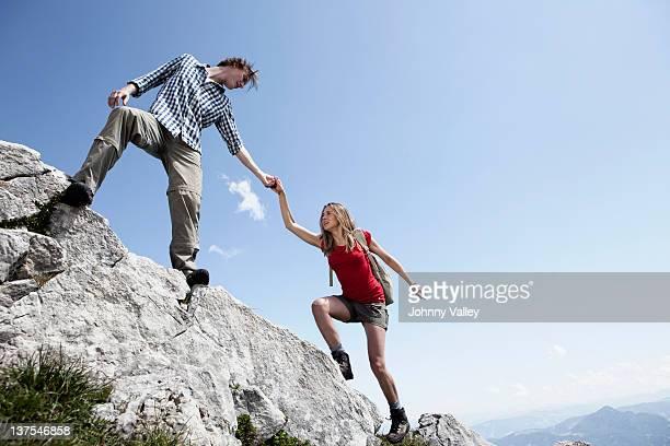 Paar Klettern felsigen Hügel
