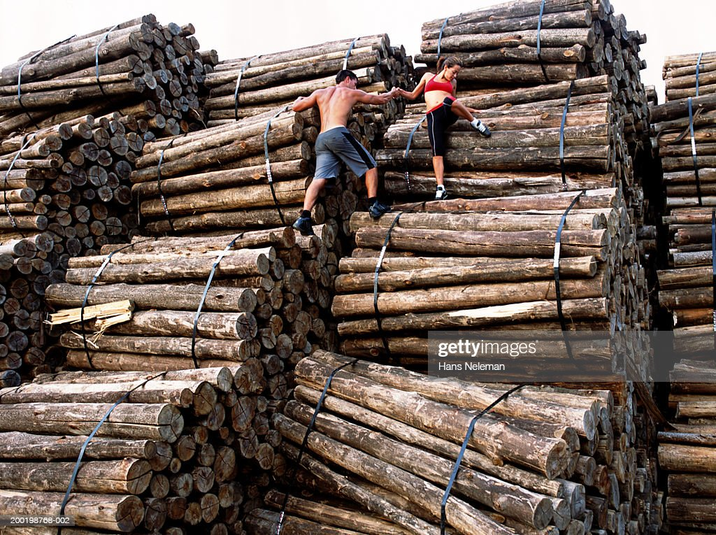 Couple climbing stack of bound logs, rear view, low angle view : Stock Photo