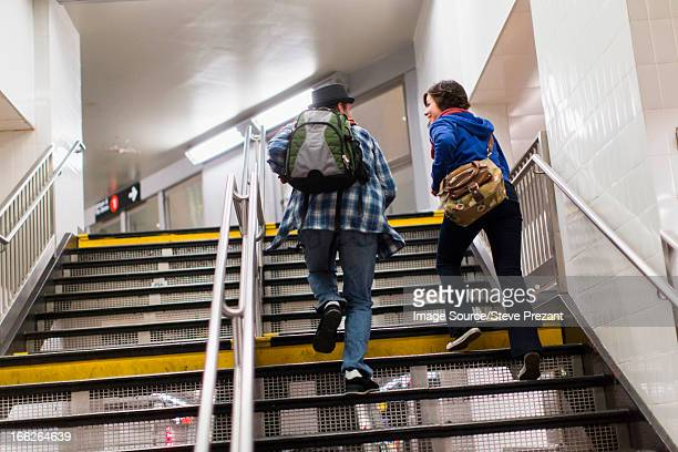 Couple climbing subway steps