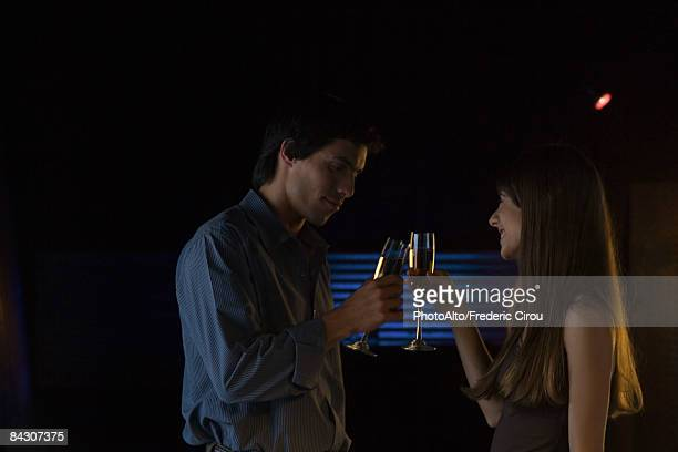 Couple clinking glasses in darkly lit room, smiling