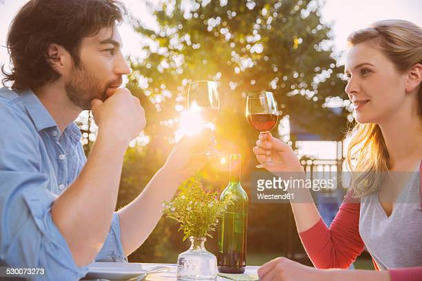 Couple clinking red wine glasses at table in evening light