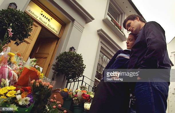 A couple comfort each other after laying flowers at the entrance to Abbey Road Recording Studios December 2 2001 after the death of musician George...