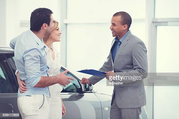 Couple communicating with car sales person.