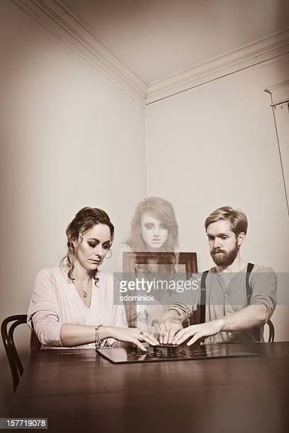 Couple Communicating With Spirit of Young Woman
