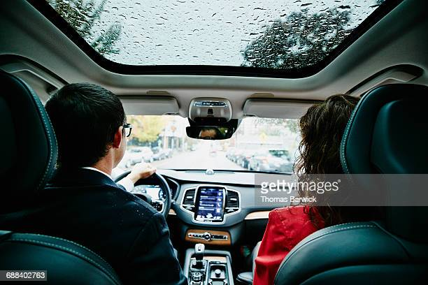 Couple commuting to work in car on rainy morning