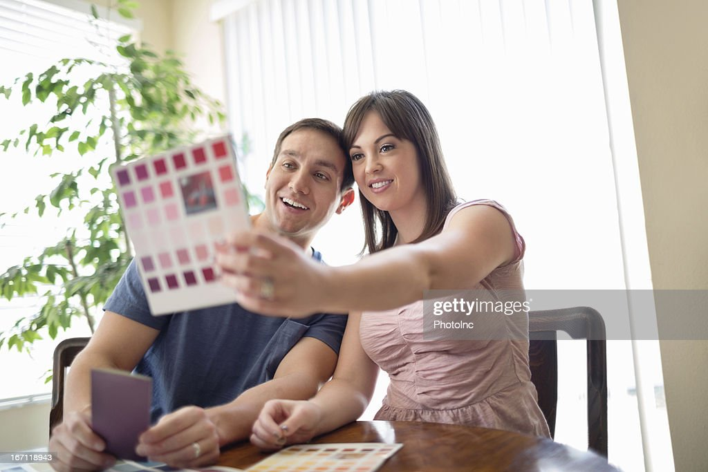 Couple Comparing Color Swatch At Table