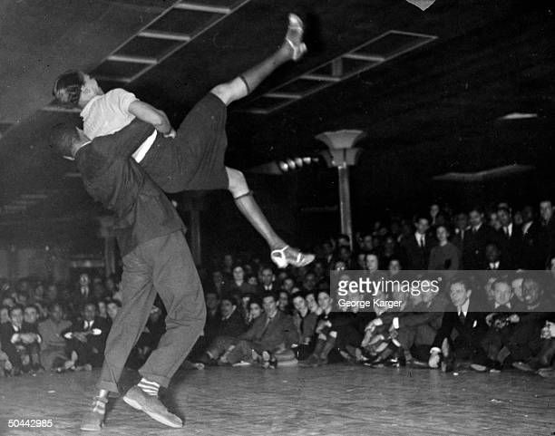 Couple competing in Savoy Ballroom Lindy Hop contest as crowd looks on