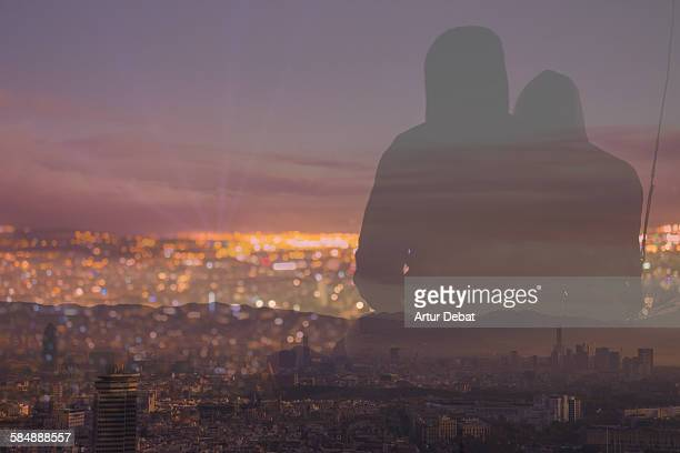 Couple contemplating Barcelona cityscape at night