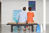Couple contemplating paintings in gallery