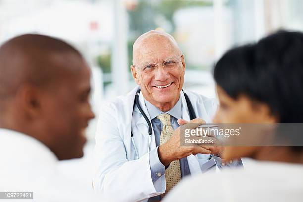 Couple conversing in front of a smiling senior doctor