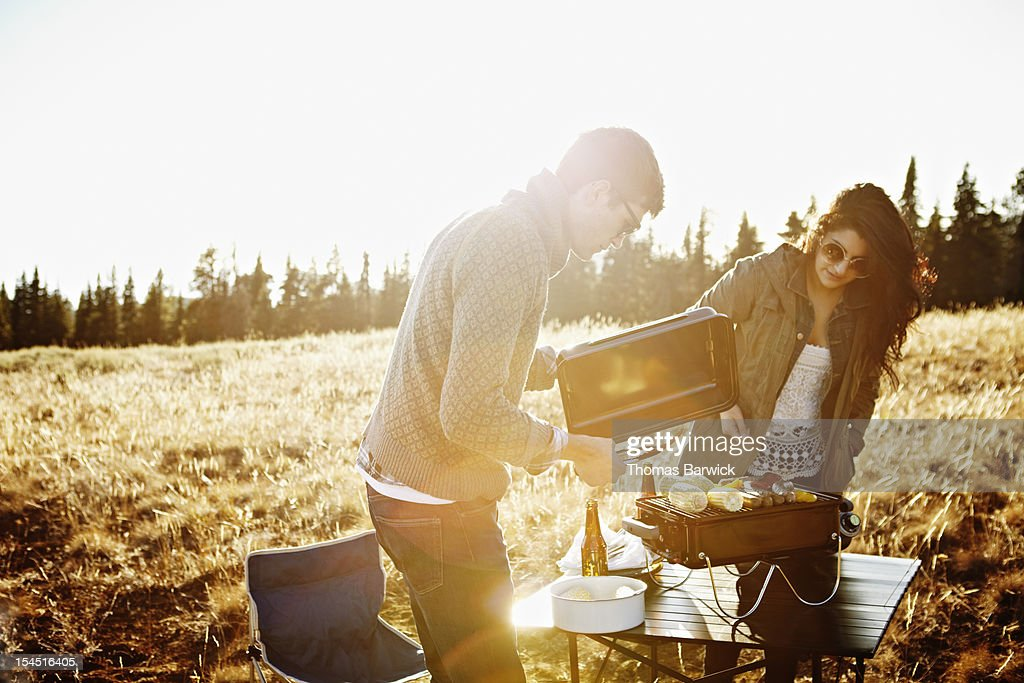 Couple cooking at barbecue in field at sunset : Stock Photo