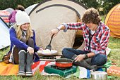 Couple cooking food at campsite