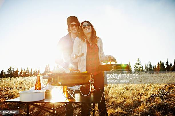 Couple cooking on barbecue in field at sunset