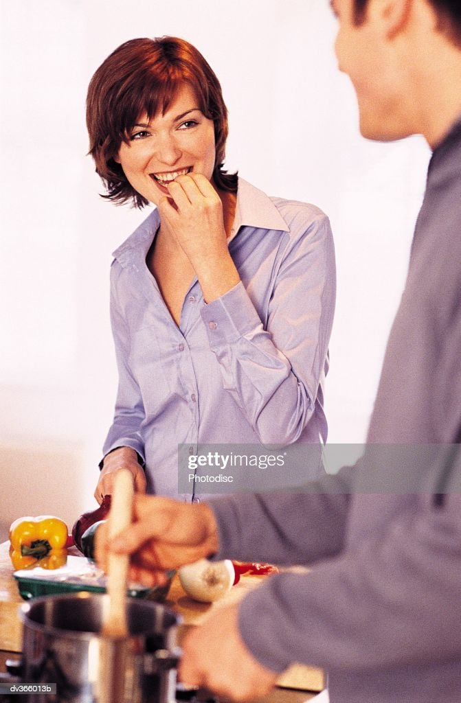 Couple cooking, woman tasting vegetables : Stock Photo