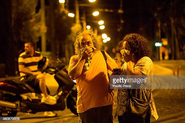 A couple cover their face due to tear gas smoke Unions gather in Syntagma square to protest against the voting of the new austerity measures by...