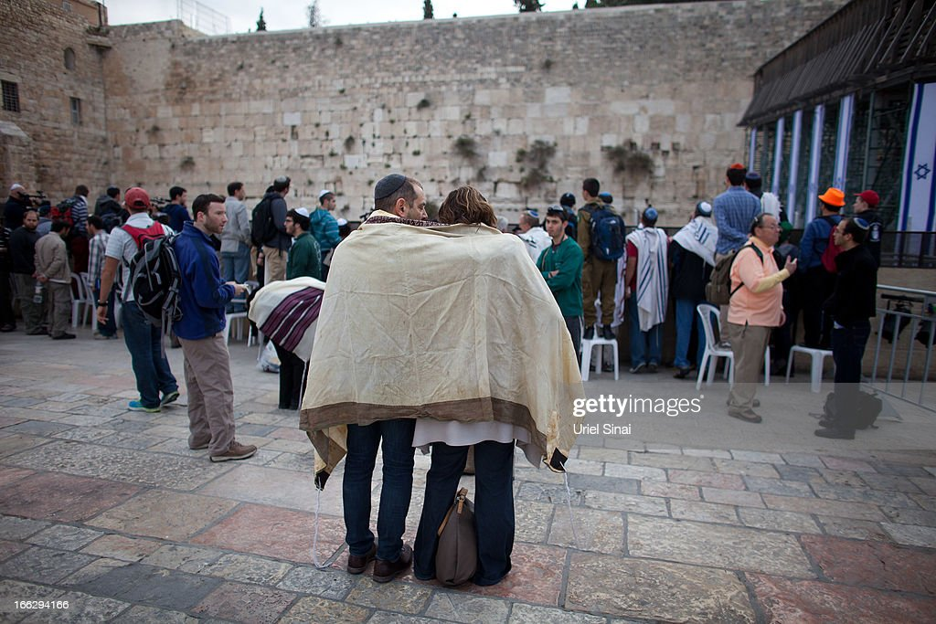 A couple covered with a 'Tallit' (traditional Jewish prayer shawl) pray as member of the religious group 'Women of the Wall' pray at the Western Wall on April 11, 2013 in Jerusalem's Old City, Israel. Five members of the organisation 'Women of the Wall' were detained by police during the group's monthly prayer at the Western Wall, after covering themselves with prayer shawls in contradiction to the holy site's custom.